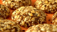 Delicious yummy freshly baked homemade oatmeal cookies rotating on a orange bamboo plate. Looped video