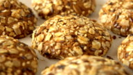 Delicious yummy freshly baked homemade oatmeal cookies rotating on a white bamboo plate. Looped video