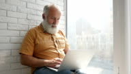 Delighted senior man texting on his laptop video