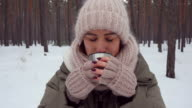 Delightful young woman in a warm outfit blowing on hot beverage to cool it down video