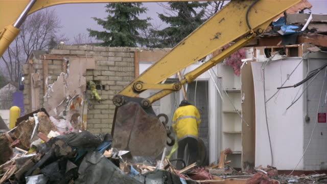 Demolition of building by excavator in progress. Construction site. video