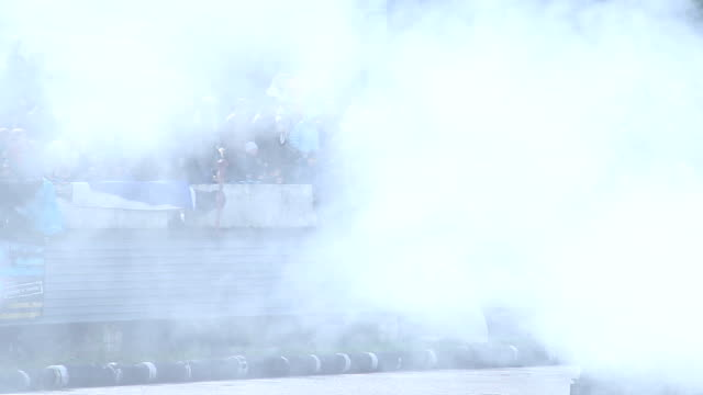 Dense smoke hovering above people at extreme car stunt show video