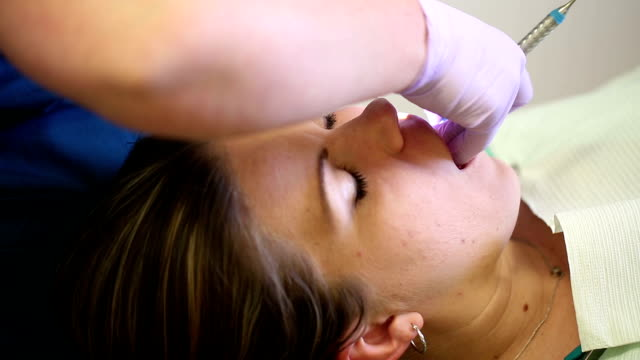 Dental Cleaning on Female Patient Tilt Down from Dentist video
