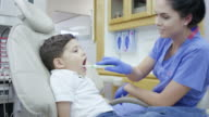 Dental hygienist working on a small child sitting in a dental chair brushing his teeth video