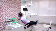 Dental unit in cabinet, with a man lying on her patients, interior of dental office video