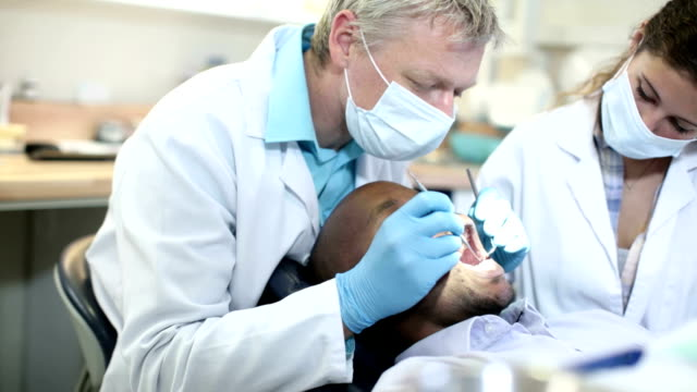 Dentist and assistant cleaning patients illuminated mouth. video