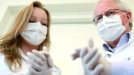 Dentist and assistant rubbing hands looking at the camera sinisterly video