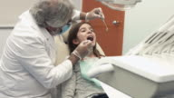 Dentist checking girl's mouth with instruments in dental chair video