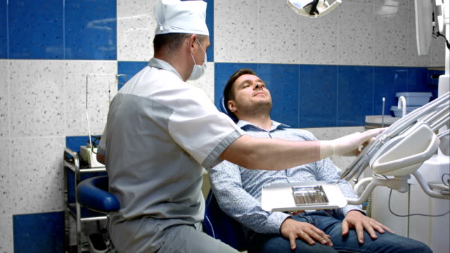 Dentist detects the carious teeth of the patient on the dentist chair video