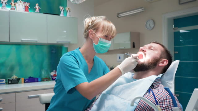 Dentist examining patient's teeth and looking to the camera. video
