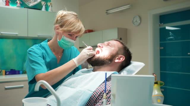 Dentist examining patient's teeth, explains him procedure. Slider shot, left. video