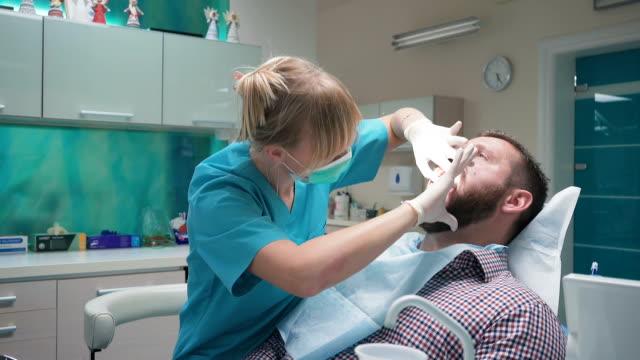 Dentist examining patient's teeth, explains him procedure. Steadicam. video