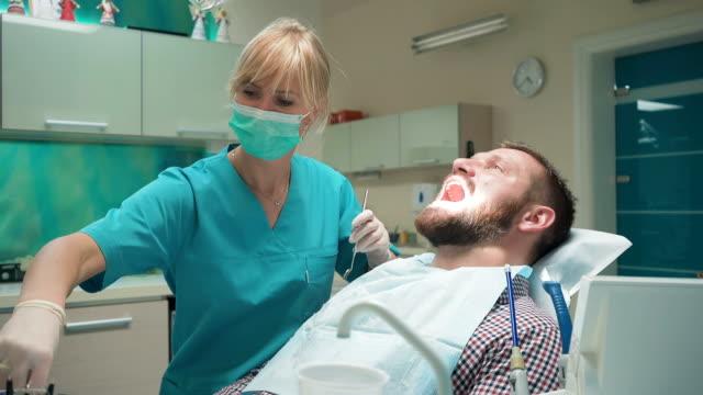 Dentist examining patient's teeth, explains him procedure. video