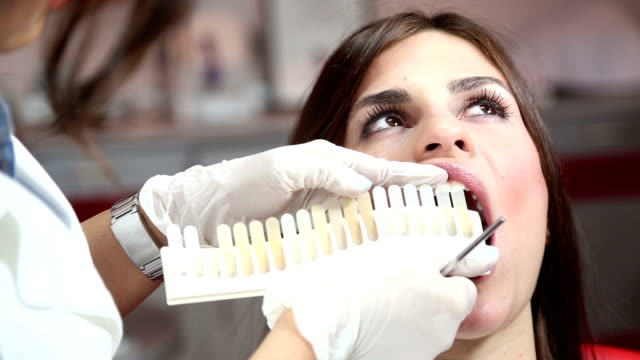 Dentist examining whiteness of patient teeth video