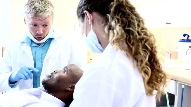Dentist explaining something to patient whilst reassuring him. video