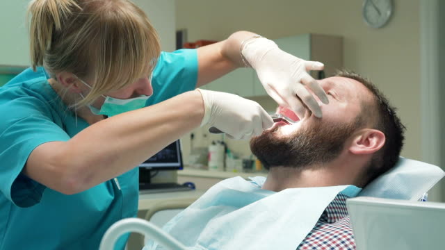 Dentist extracting patient's tooth and looking to camera. Close shot. video