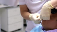 Dentist hands with white gloves holding impression material in patient's mouth men for a dental cast video