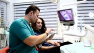 Dentist informing patient via digital tablet video