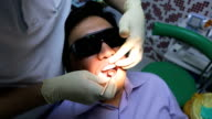 Dentist is healing client teeth with mouth mirror video