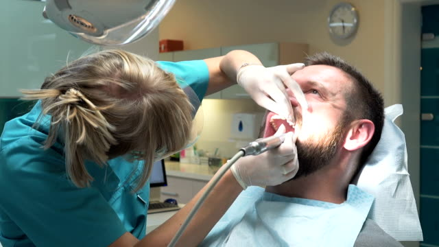 Dentist polishing teeth of young client. Steadicam. video