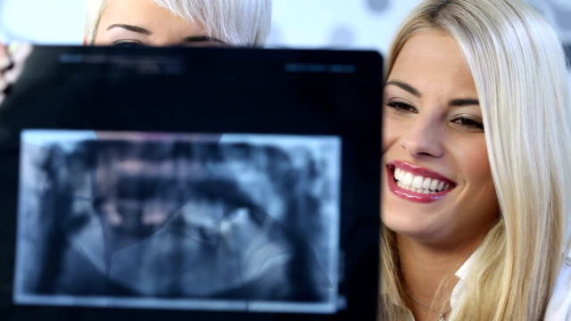Dentist showing female patient x-rays video