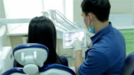 Dentist shows a patient x-ray on the tablet of her teeth video