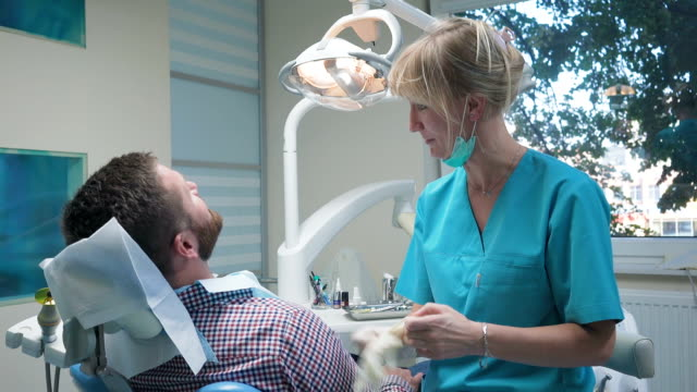 Dentist wearing gloves and examining patient's tooth. Steadicam shot. video