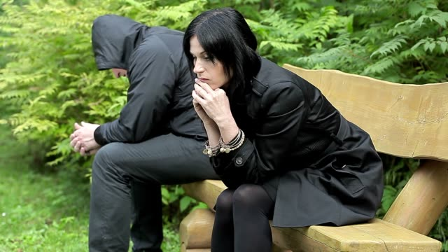 Depressed couple sitting on bench in the park video