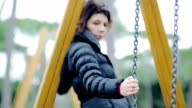 Depressed girl on a swing in the autumn park video