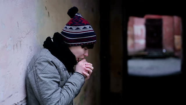 Depressed guy suffering from cold and loneliness in strange abandoned video