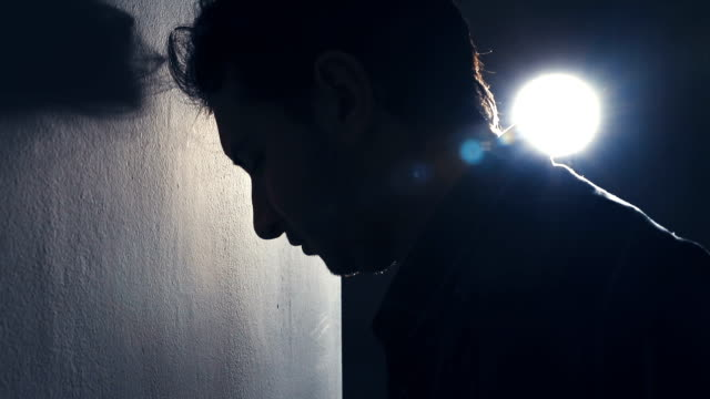 Depressed man leaning his head against a wall video