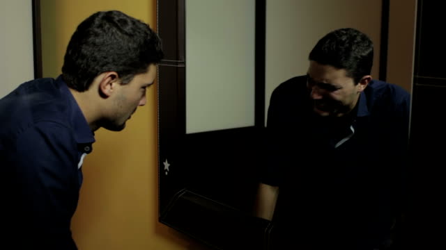Depressed man looking in the mirror at his angry reflection video