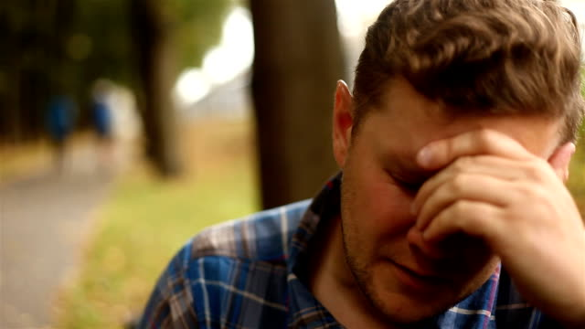 Depressed, sad young man sitting in the park video