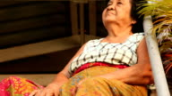 Depressed senior asian woman sitting in home video