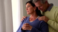 Depressed senior wife standing by window with husband video