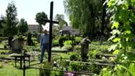 Depressed widower man sit on bench near wife tomb in sorrow. FullHD video