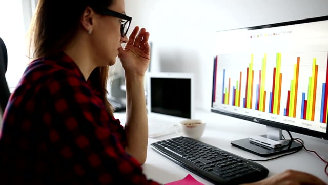 Depressed young woman using computer at the office video