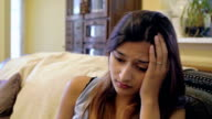 Depressed young woman with head in hands, grieving or sad video