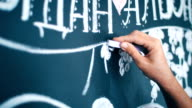 designer at work: the girl's hand draws a chalk on a blackboard video