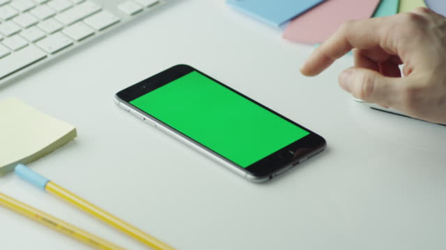 Designer is Using Mobile Phone with Green Screen in Portrait Mode. video
