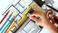 Designer's hand working with home floor plan video