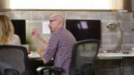 Designers Working At Desks In Modern Office Shot On R3D video