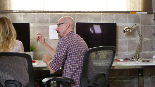 Designers Working At Desks In Modern Office Shot On R3D video