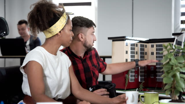 Designers working with model of building using VR video