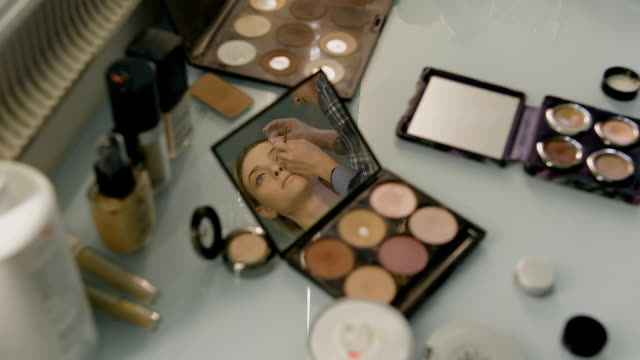 Desk in a beauty salon. reflected in the mirror of her compact face of the girl. Professional Stylist video