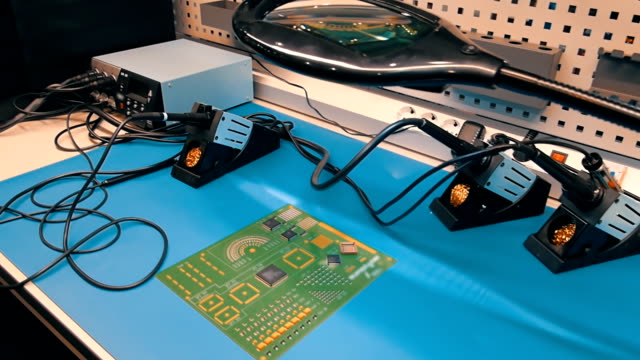 Desk with a magnifying glass and three soldering Iron for work with PCB video