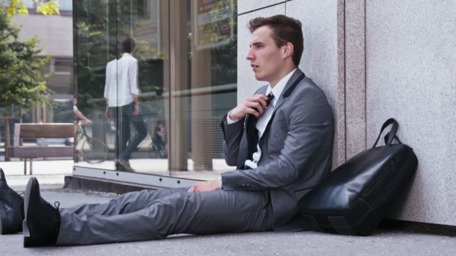 Desperate businessman sitting on the street video