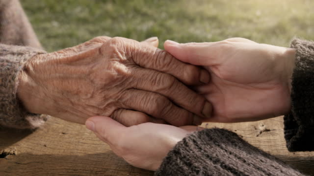 A HELPING HAND. Detail of a Young Woman Hands Holding the Senior Woman Hands video