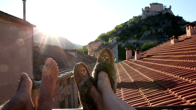 Detail of couple's feet relaxing on medieval rooftop terrace video