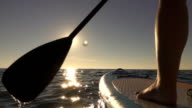 CLOSE UP: Detail of paddling stand up paddleboard through sparkling ocean water video